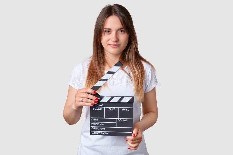 Conceito do cinema A jovem mulher atrativa com cabelo longo, guarda o clapperboard, tem o tratamento de mãos vermelho, vestido na imagem de stock