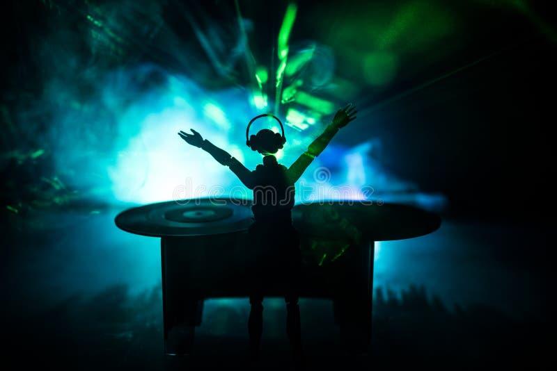 Conceito do clube do DJ Mulher DJ que mistura, e riscando em um clube noturno Silhueta da menina na plataforma do DJ, nas luzes d foto de stock
