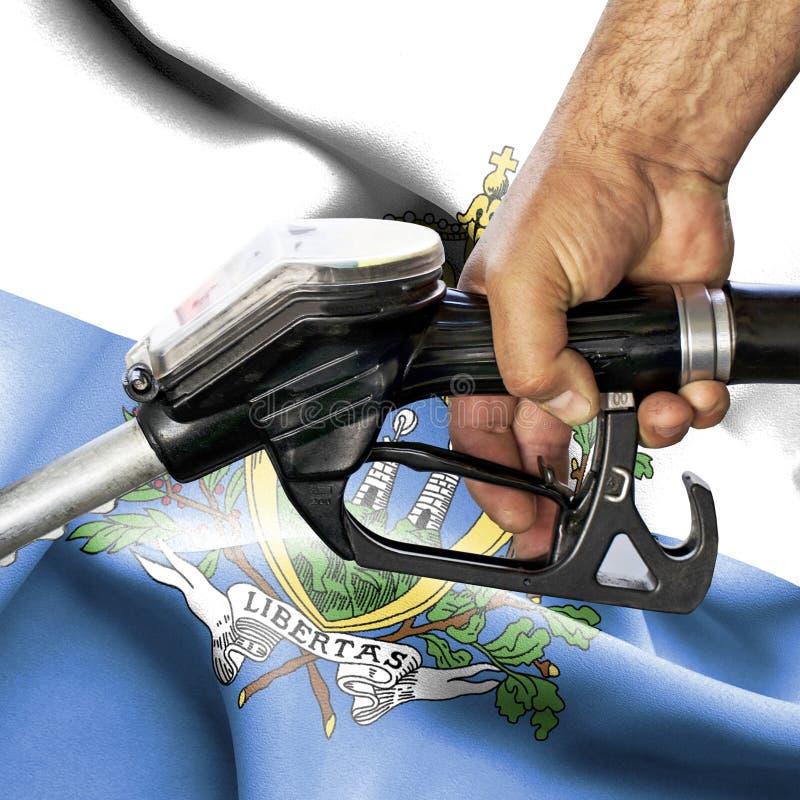 Conceito do consumo da gasolina - mangueira da terra arrendada da mão contra a bandeira de São Marino fotografia de stock