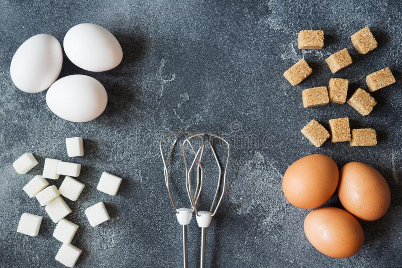 Conceito do cozimento, dos ovos e do açúcar de casa com um batedor de ovos em um foco seletivo da tabela escura imagem de stock