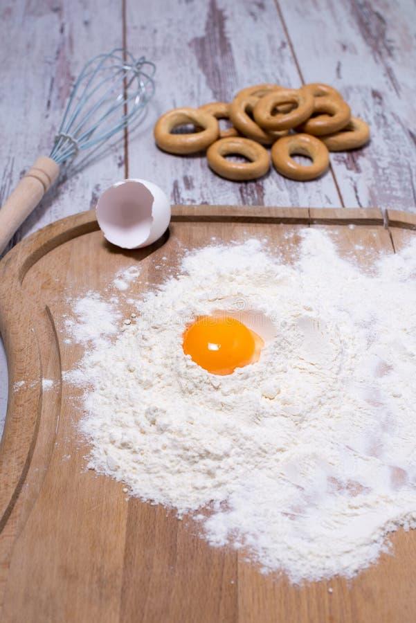 Conceito do cozimento Farinha e ovos polvilhados na placa de corte de madeira, cozinhando ingredientes Prepare fazendo a massa de imagem de stock royalty free