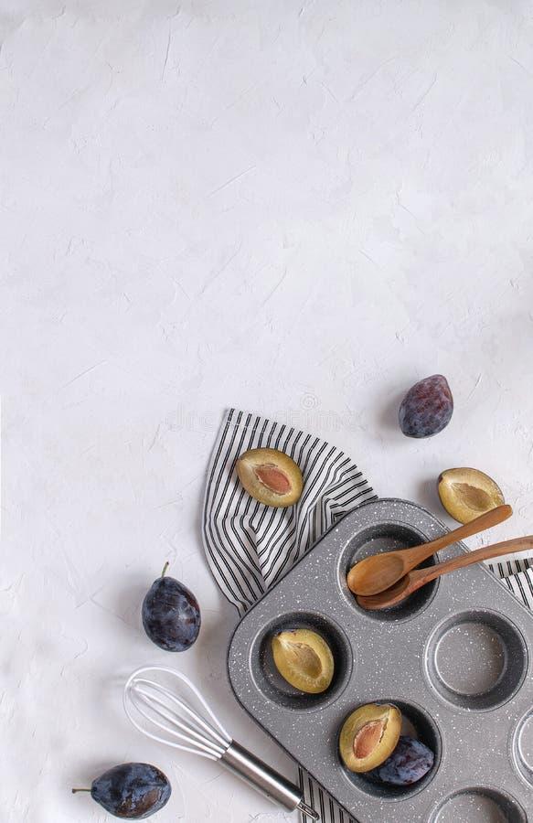 Conceito do cozimento do outono - ameixas frescas, molde de metal do queque, batedor de ovos, imagem de stock royalty free