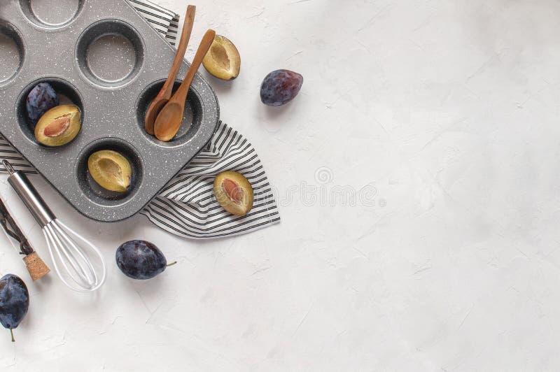 Conceito do cozimento do outono - ameixas frescas, molde de metal do queque, batedor de ovos, fotografia de stock