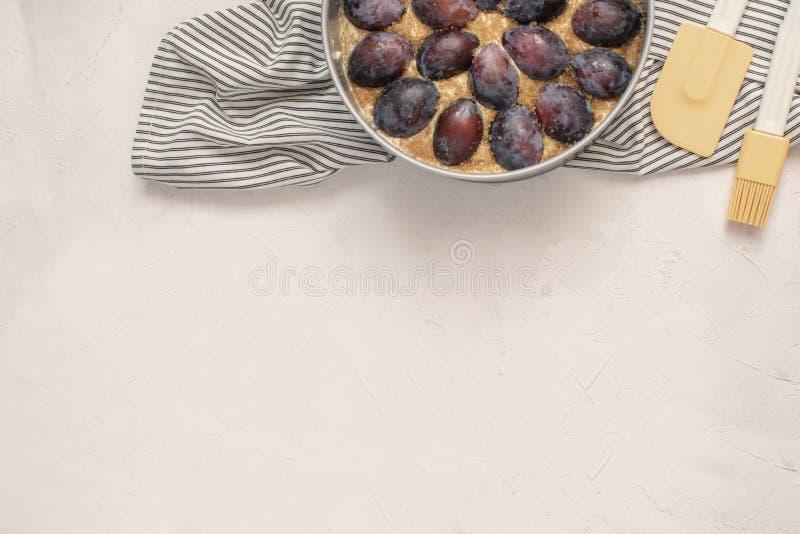 Conceito do cozimento do outono - torta cru da ameixa no molde de metal, silicone imagens de stock royalty free