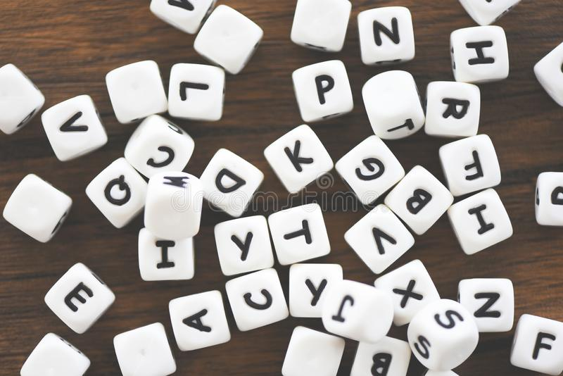 Conceito do cubo dos dados do texto - a letra corta o alfabeto no fundo de madeira fotografia de stock