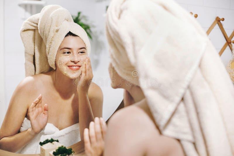 Conceito do cuidado de pele A mulher feliz nova na toalha que faz a massagem facial com cara orgânica esfrega e que olha o espelh foto de stock