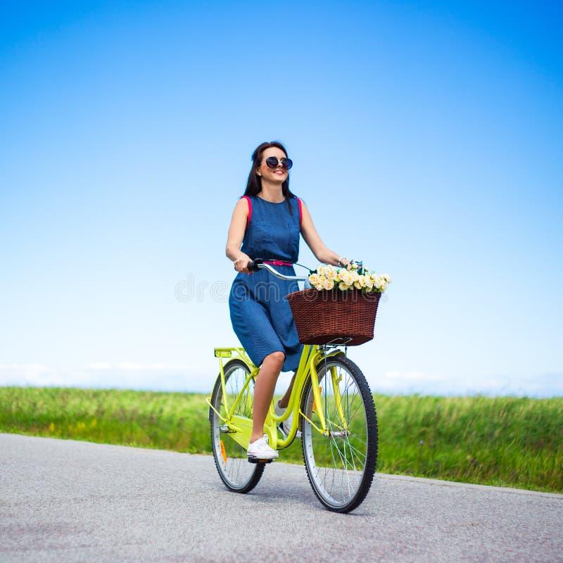 Conceito do curso - bicicleta do vintage da equitação da mulher com a cesta no cou imagens de stock