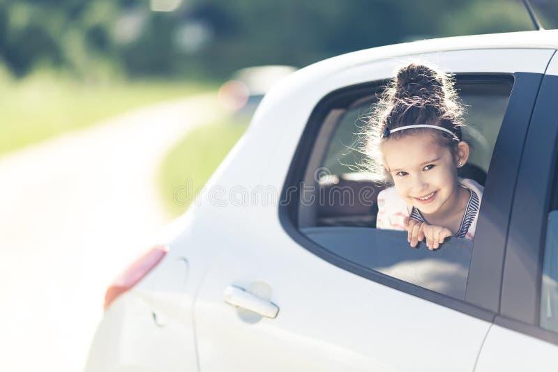 Conceito do curso da família pelo carro Menina de sorriso feliz da criança que olha da janela de carro com estrada borrada Fundo  imagens de stock