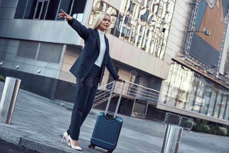 Conceito do curso e da viagem de negócios Jovem mulher de sorriso com o táxi de travamento do saco do curso imagem de stock royalty free