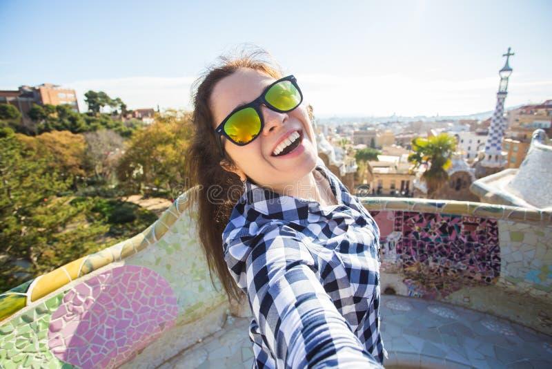 Conceito do curso e dos feriados - jovem mulher bonita que olha a câmera que toma a foto com o telefone esperto que sorri no parq imagem de stock royalty free