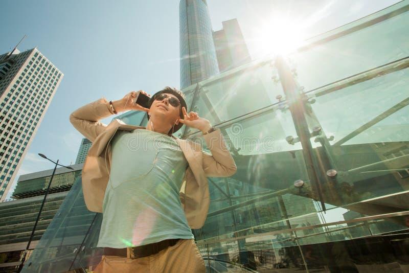 Conceito do curso e do estilo de vida Forme o homem que escuta a música no telefone e que dança na perspectiva dos arranha-céus fotografia de stock royalty free