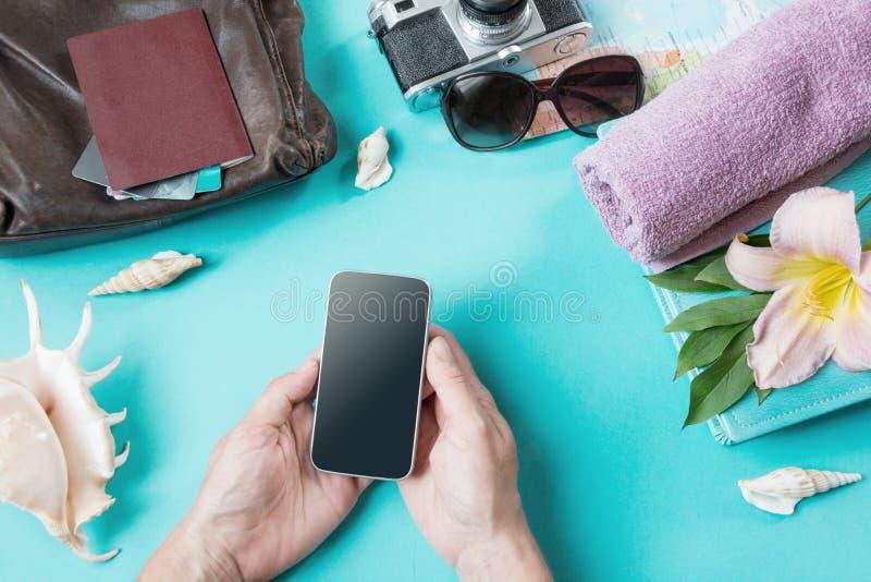 conceito do curso Mãos fêmeas com smartphone Acessórios das coisas e do verão da embalagem para uma viagem no azul pastel Vista d imagem de stock