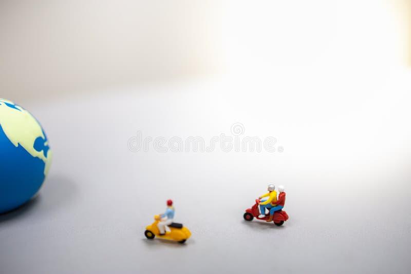 conceito do curso O grupo de figuras diminutas do viajante monta a motocicleta/'trotinette' à mini bola do mundo fotos de stock