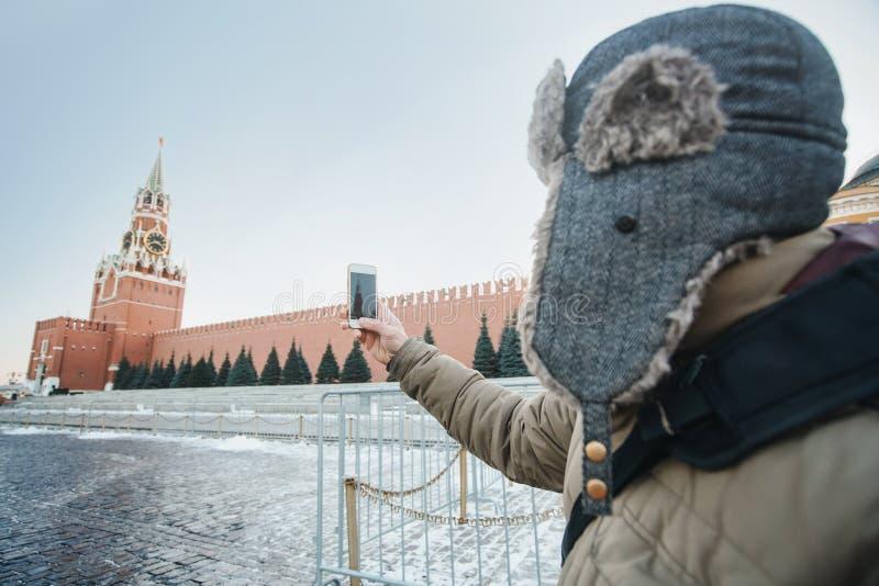 Conceito do curso O turista em um tampão faz fotos em sua paisagem de Moscou do telefone com a catedral da intercessão do Kremlin imagens de stock