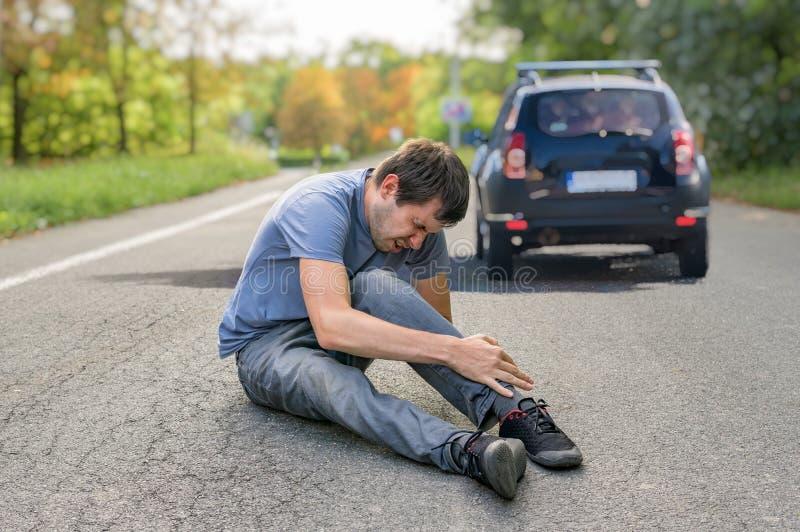 Conceito do de esticão Homem ferido na estrada na frente de um carro imagens de stock