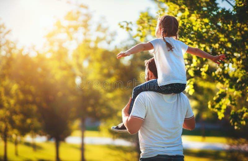 Conceito do dia de pai! paizinho da família e filha felizes da criança para trás na natureza