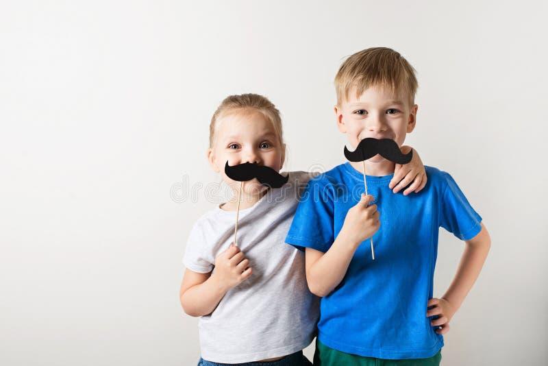Conceito do dia de pais, duas crian?as caucasianos pequenas que sorriem com o bigode no fundo branco imagens de stock