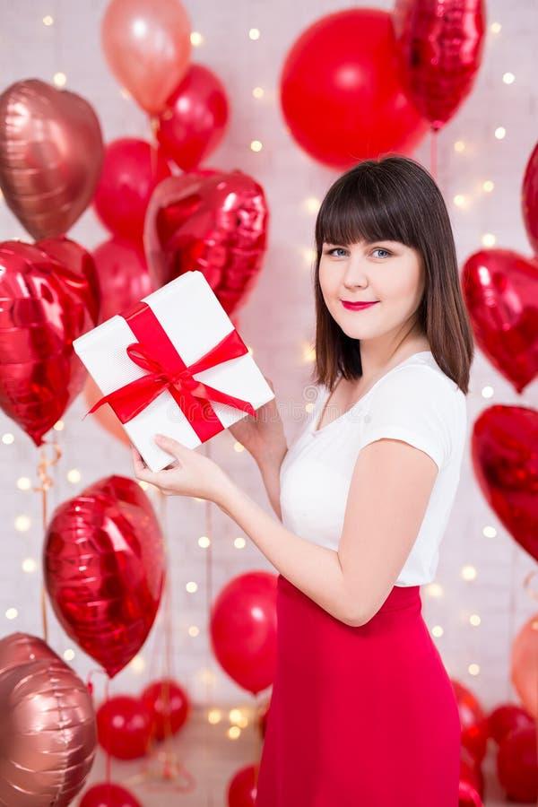 Conceito do dia de Valentim - caixa de presente bonita nova da terra arrendada da mulher sobre o fundo vermelho dos balões imagens de stock