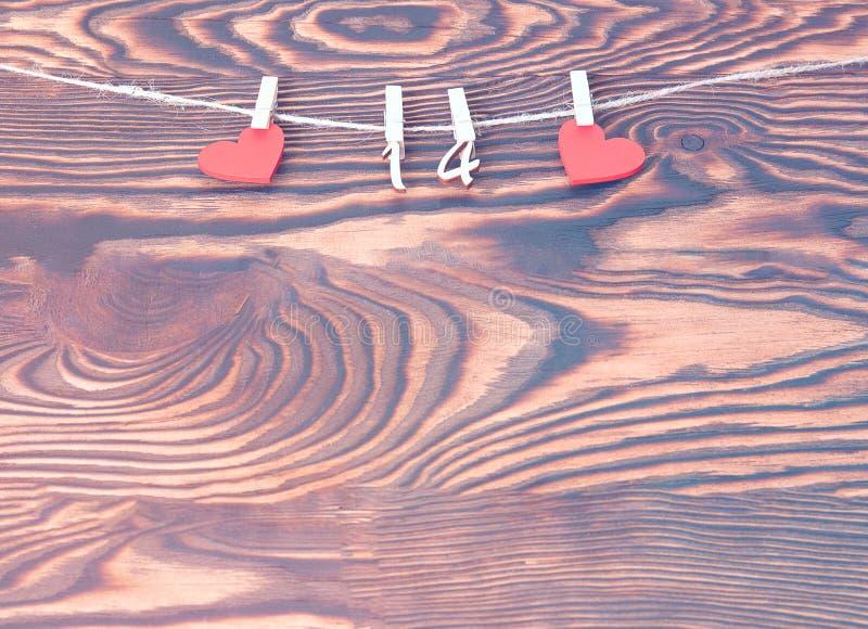 Conceito do dia de Valentim, cartão Corações de madeira vermelhos com os pinos com figuras de FEVEREIRO 14 que penduram na corda  imagens de stock royalty free