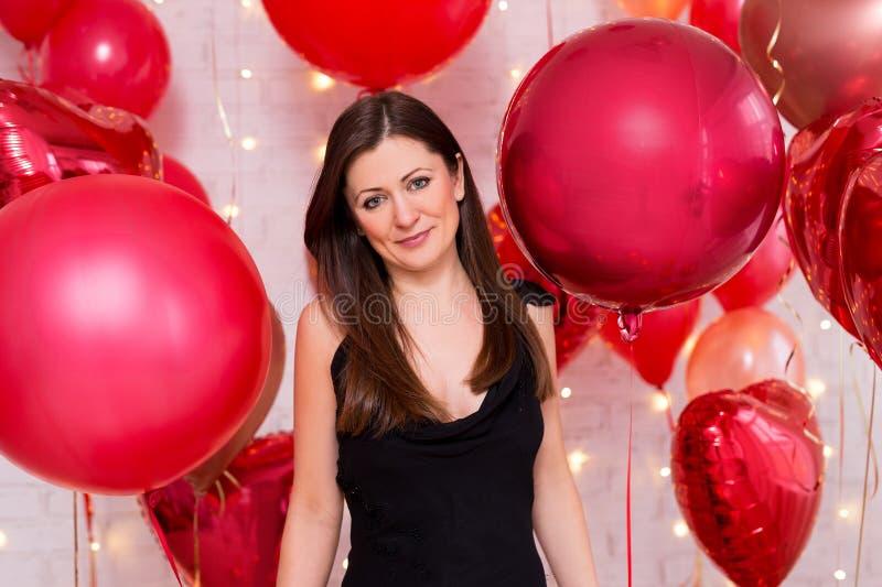 Conceito do dia de Valentim - retrato da mulher bonita no preto com os balões de ar vermelhos fotografia de stock royalty free