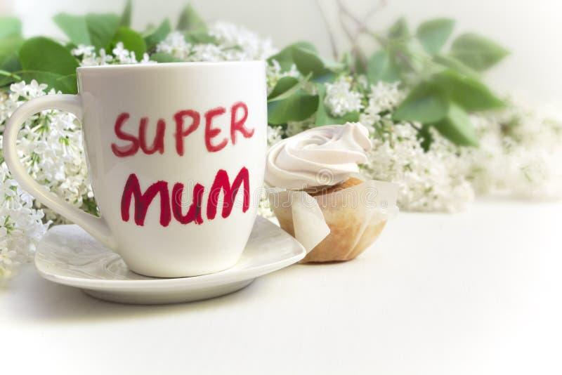 Conceito do dia do ` s da matriz Agrida com ` super do mum do ` da inscrição, queque e flores do lilás imagens de stock