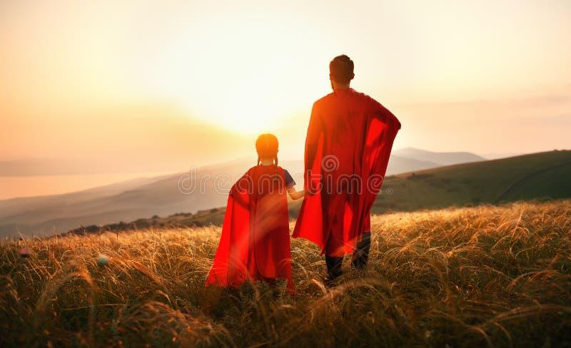 Conceito do dia do ` s do pai filha do paizinho e da criança no traje do super-herói do herói no por do sol imagem de stock