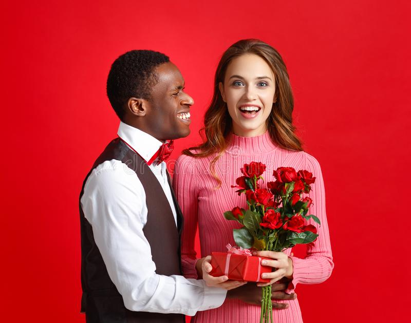 Conceito do dia do ` s do Valentim pares novos felizes com coração, flores, presente no vermelho fotografia de stock royalty free