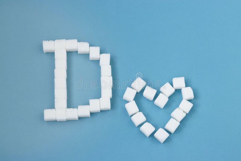 Conceito do diabetes: uma letra grande D e um coração feito dos cubos do açúcar no fundo azul imagem de stock