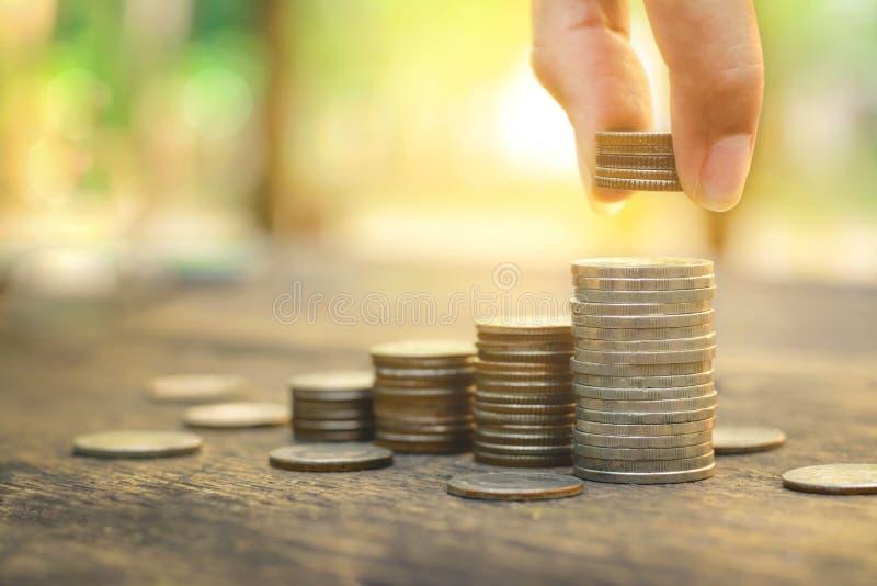 Conceito do dinheiro da economia com a mão que põe o negócio crescente da pilha da moeda do dinheiro sobre o fundo do por do sol fotos de stock royalty free