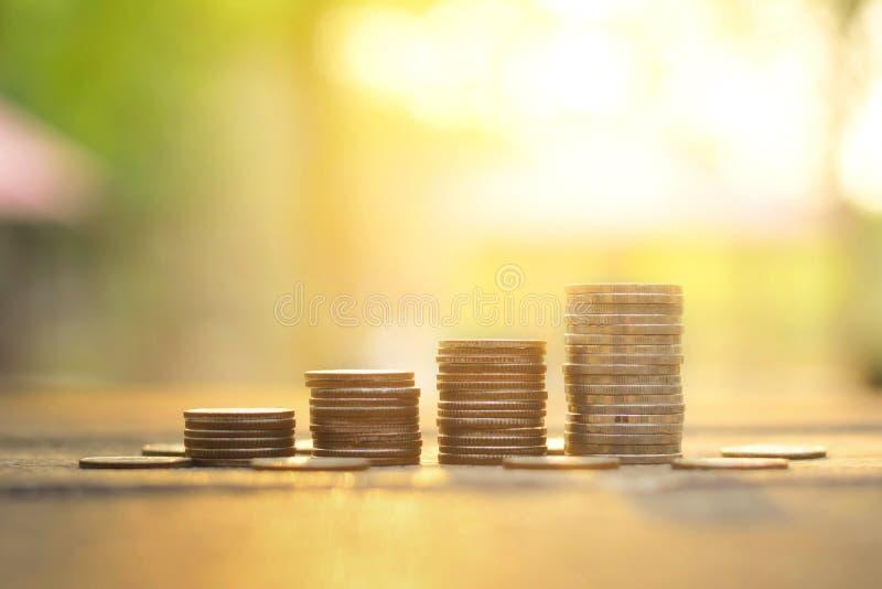 Conceito do dinheiro da economia com negócio crescente da pilha da moeda no fundo do por do sol fotos de stock