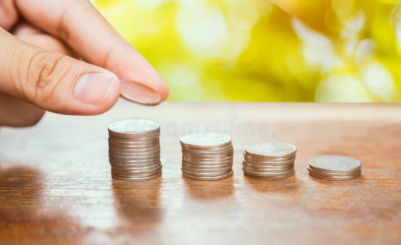Conceito do dinheiro da economia, mão masculina que põe a pilha da moeda do dinheiro fotografia de stock