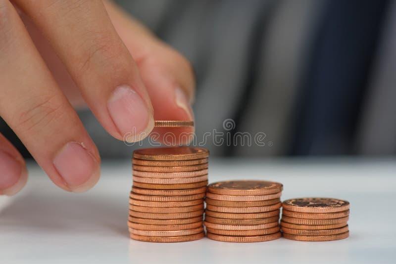 Conceito do dinheiro da economia pré-ajustado pela mão masculina que põe o stac da moeda do dinheiro imagem de stock royalty free