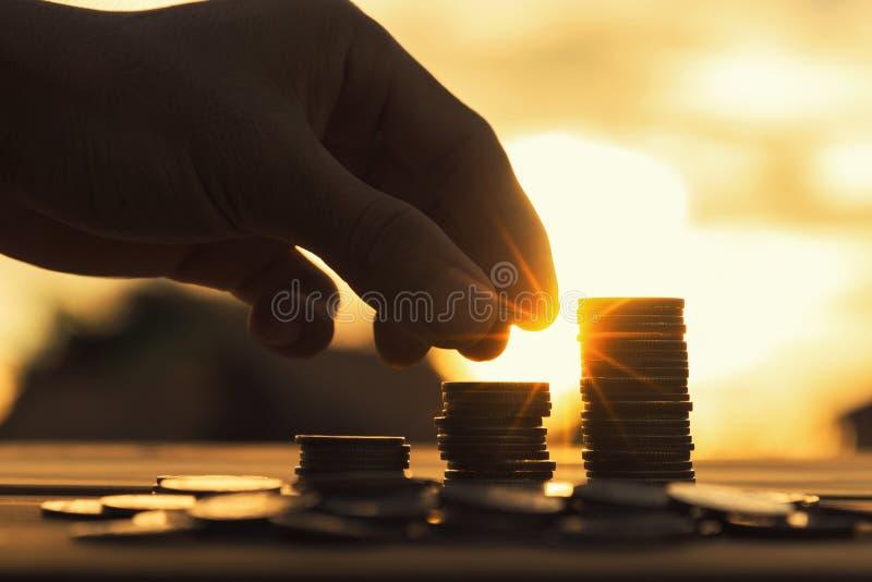 Conceito do dinheiro da economia pré-ajustado pela mão masculina que põe o stac da moeda do dinheiro foto de stock royalty free