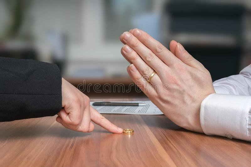 Conceito do divórcio A esposa está retornando o anel a seu marido desapontado fotos de stock royalty free