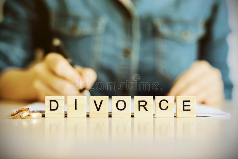 Conceito do divórcio O divórcio da palavra com alianças de casamento imagens de stock royalty free