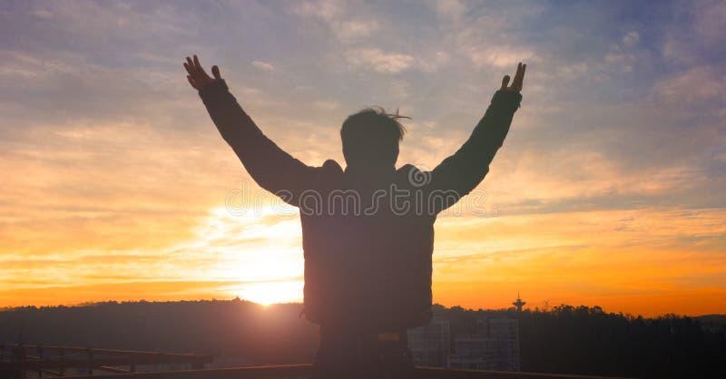 Conceito do elogio e da adoração: Mostre em silhueta o ser humano que levanta as mãos para o deus rezando na cruz borrada com a c imagem de stock