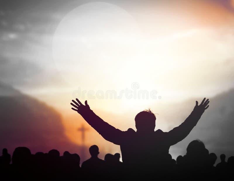 Conceito do elogio e da adoração: Silhueta das orações cristãs que levantam a mão ao rezar a Jesus imagens de stock