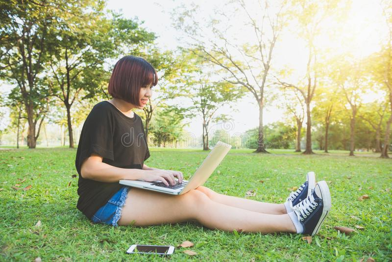 Conceito do ensino distância Mulher asiática nova do moderno feliz que trabalha no portátil no parque Estudo na grama imagem de stock royalty free
