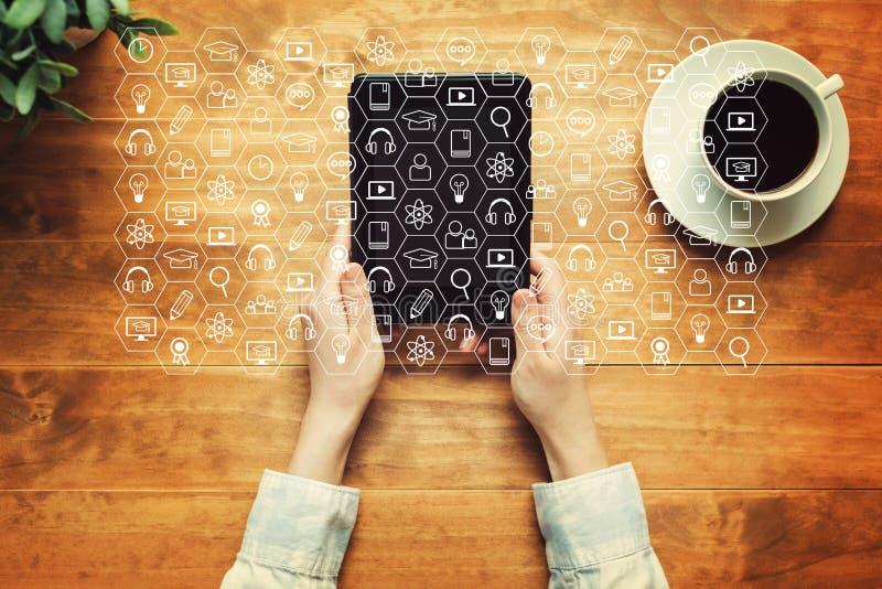 Conceito do ensino eletrónico com uma pessoa que guarda uma tabuleta foto de stock royalty free