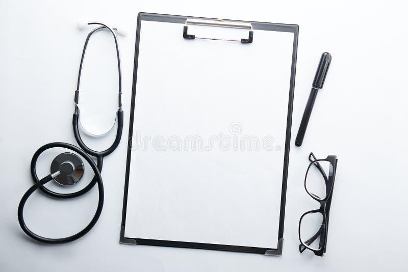 Conceito do equipamento médico e da tecnologia Anamnese e estetoscópio imagem de stock