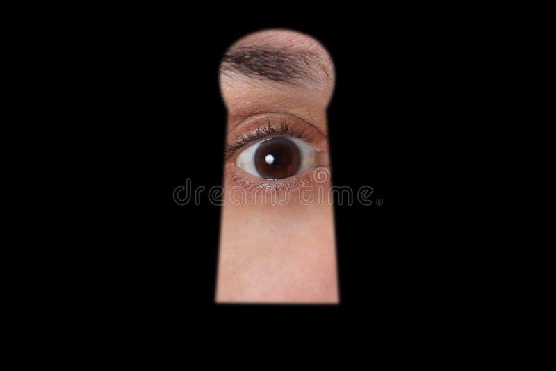 Conceito do espião: espião do olho através de um buraco da fechadura com espaço da cópia para seu texto imagem de stock