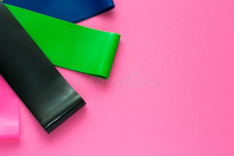 Conceito do esporte - ajuste dos expansores elásticos da aptidão colorida para a mulher no fundo cor-de-rosa Perda saudável do es foto de stock