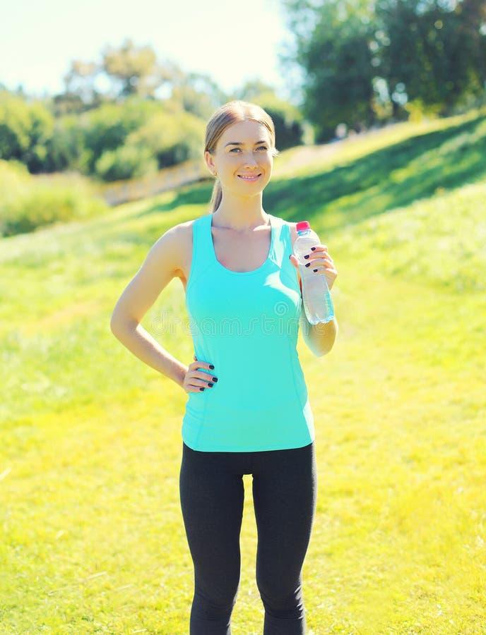 Conceito do esporte e da aptidão - água potável de sorriso bonita da jovem mulher da garrafa no parque foto de stock