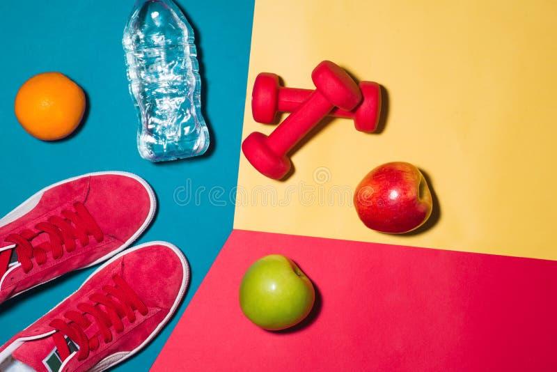 Conceito do esporte Equipamento da aptidão Sapatilhas, água, maçã, dumbbe imagem de stock