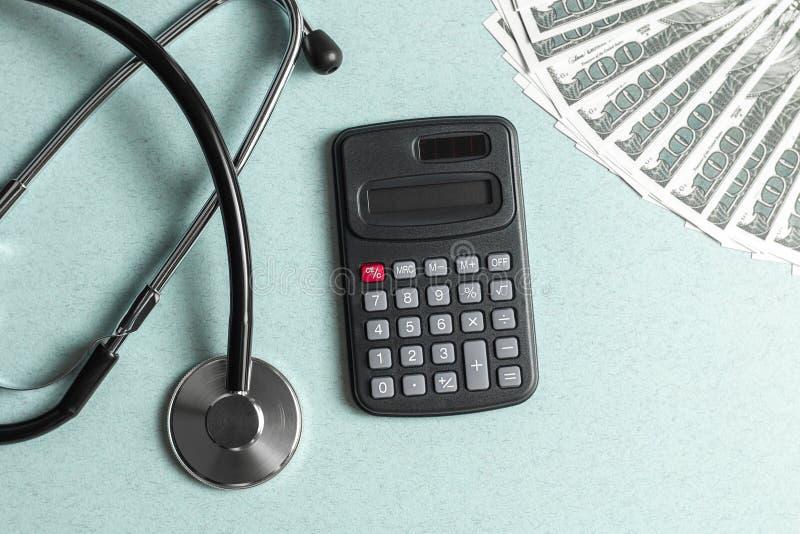 Conceito do estetosc?pio, do dinheiro e da calculadora Medicina paga Custos do seguro de sa?de imagem de stock royalty free