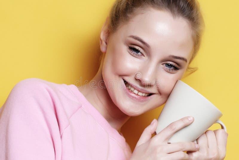 Conceito do estilo de vida, do alimento e dos povos: café bebendo da jovem mulher sobre o fundo amarelo fotografia de stock