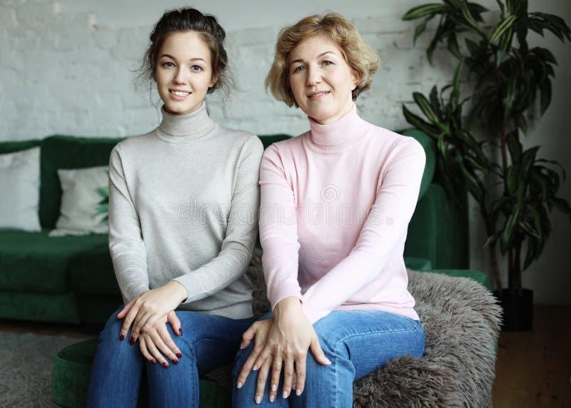 Conceito do estilo de vida, da família e dos povos: Jovem mulher feliz e sua mãe em casa imagem de stock