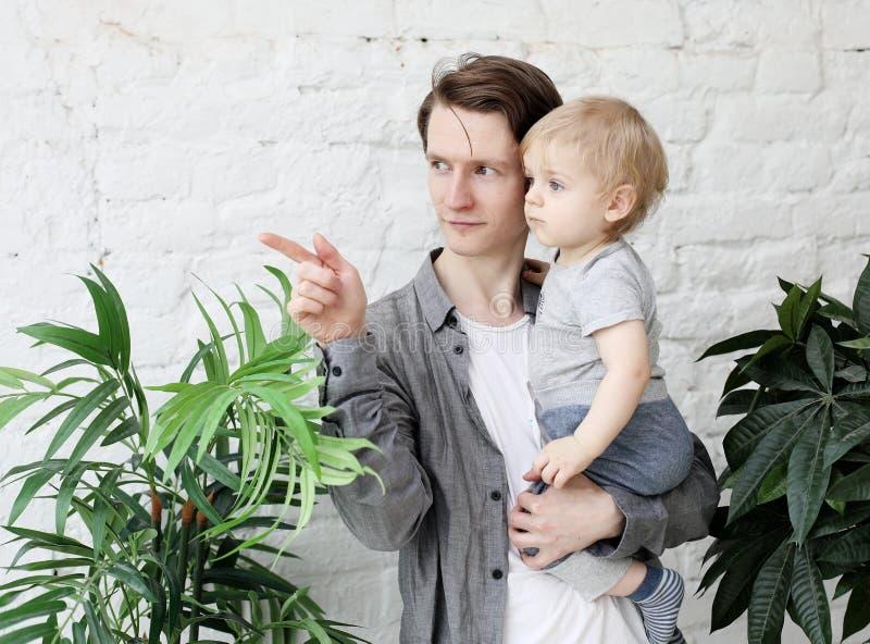 Conceito do estilo de vida, da fam?lia e dos povos - pai novo feliz com seu filho de um ano que joga em casa imagens de stock