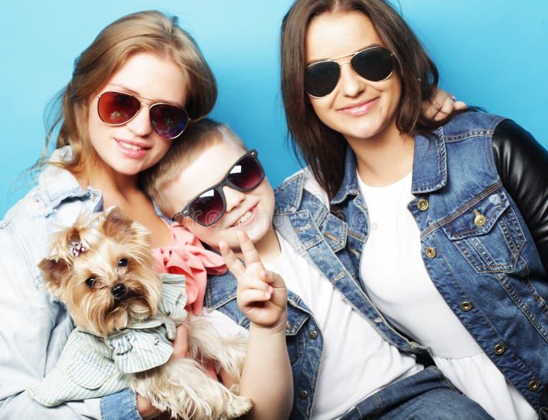 Conceito do estilo de vida, da felicidade, o emocional e dos povos: irmãs da American National Standard dois do irmão, com cão pe fotografia de stock royalty free