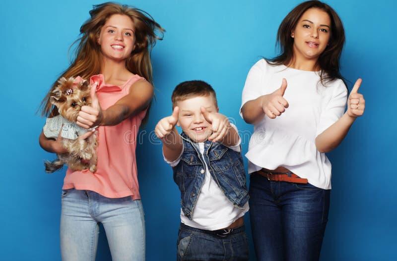 Conceito do estilo de vida, da felicidade, o emocional e dos povos: irmãs da American National Standard dois do irmão, com cão pe fotografia de stock